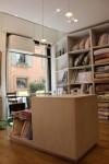 negozio biancheria stile moderno con cassa in laminato legno e cristallo, elementi d'arredo in laminato legno, design fc arredamenti
